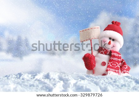 Winter arrival concept with Snowman with a blank placard in his hand. Dressed with red scarf and gloves and hat in the snow outside under the snow. Front view. Horizontal composition - stock photo