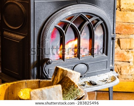 Winter at home. Closeup of fireplace with orange fire flame and firewood in the barrel interior. Heating. - stock photo