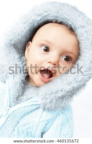 Winter baby girl wearing a faux fur knitted jacket covered in snow flakes