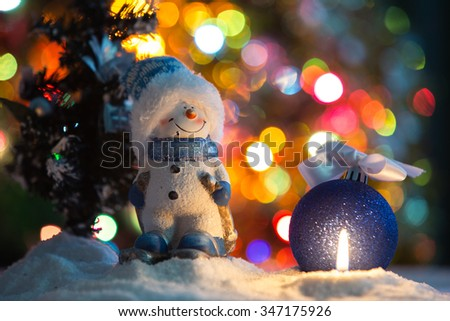 Winter background. Christmas background. Christmas snowman and candles. Close-up. Night Photography. - stock photo
