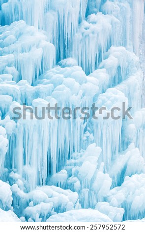 Winter background pattern and texture of a beautiful frozen waterfall or fountain with cascading icicles from dripping water in shades of white to blue - stock photo
