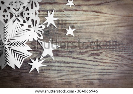 Winter background with hand-made paper snowflakes on wooden background - stock photo