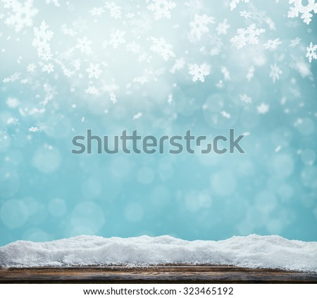 Winter background with pile of snow and blur abstract lights. Empty wooden planks on foreground. Copyspace for text - stock photo