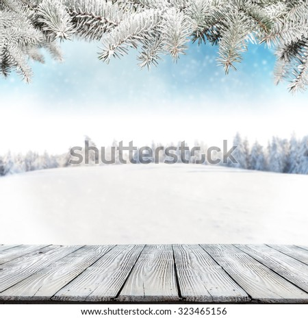 Winter background with pile of snow and blur landscape. Empty wooden planks on foreground. Copyspace for text - stock photo