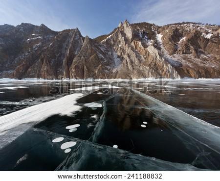 Winter Baikal - ice, snow, rocks, reflection - stock photo