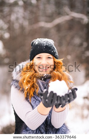 Winter beautiful girl outdoor portrait with snow in hands. Young woman ready for blowing snow at snowy trees background. Winter fun. Portrait of smiling happy girl dressed in fur vest, jumper and hat. - stock photo