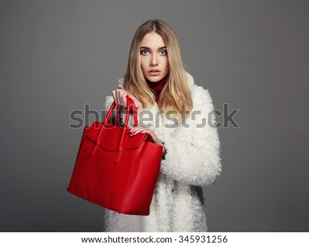 Winter beautiful Woman with red Handbag.Beauty Fashion Girl in fur. luxury stylish blonde.Shopping - stock photo