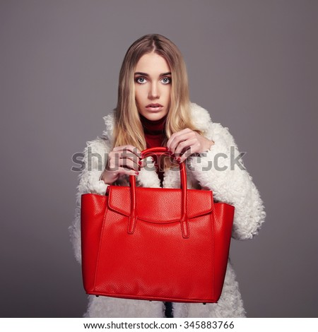 Winter beautiful Woman with red Handbag. Beauty Fashion Model Girl in fur. luxury stylish blonde. Shopping - stock photo