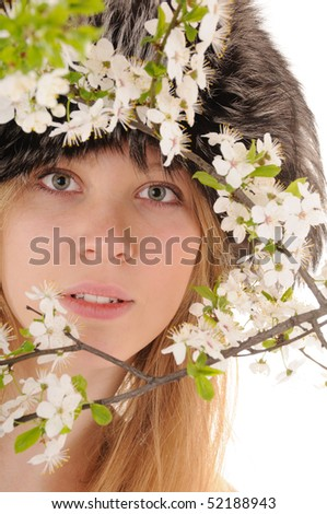 Winter beauty woman looks throught spring white cherry flowers. Focus on woman's eyes. - stock photo
