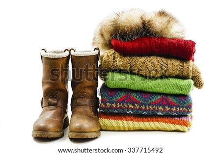 Winter boots, cap and stack of various sweaters. Winter style. Isolated on white background - stock photo