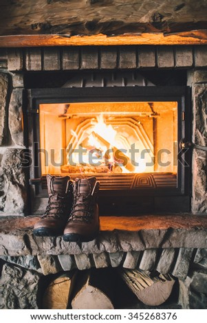 Winter boots in front of a fireplace. Pair of vintage folk boots drying near the fireside. Warm cozy fireplace in the authentic chalet. Hipster shoes getting warm near the burning fire in a cabin.