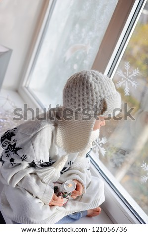 winter boy sitting by the window in a white knitted cap - stock photo