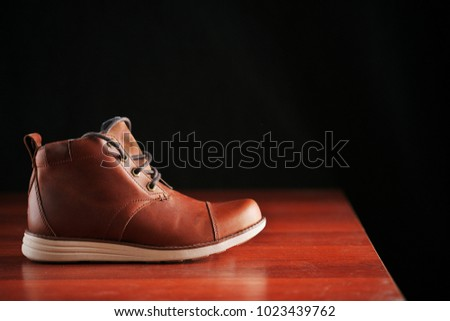 winter brown leather boots on a dark background. Modern fashion and style.