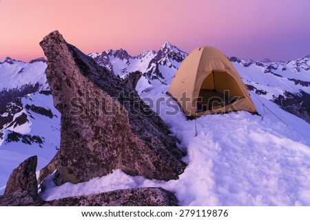 Winter camping on a summit of a mountain peak in a tent - stock photo