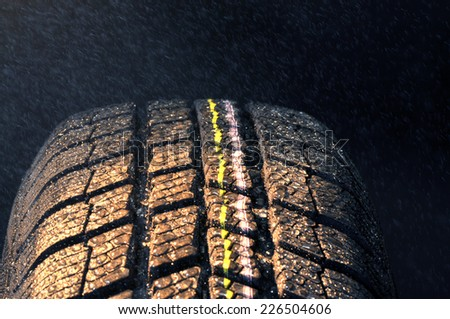 Winter car tire in rain, dark background - stock photo