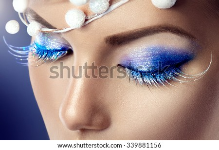 Winter Christmas eyes make up with glitter blue eyeshadows and false eyelashes. Party art model Woman makeup. Creative Girl Holiday Make-up. Snow Queen High Fashion Portrait over Blue Background - stock photo