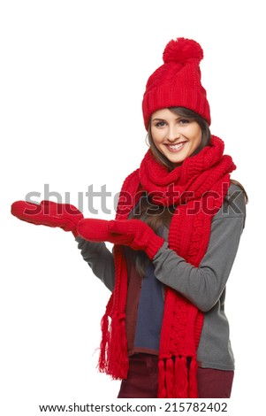 Winter, christmas, holidays concept. Smiling beautiful woman in red hat, scarf and mittens showing open hand palm with copy space for product or text, over white background - stock photo