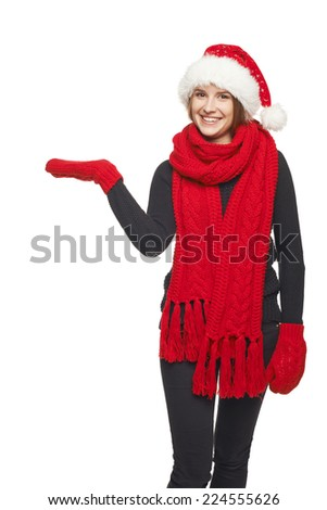 Winter, christmas, holidays concept. Smiling beautiful woman in Santa hat, scarf and mittens showing open hand palm with copy space for product or text, over gray background - stock photo