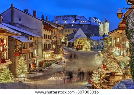Winter (Christmas) in the medieval town of Gruyeres, Fribourg canton, Switzerland. In the background looming over is the Chateau de Gruyere. - stock photo
