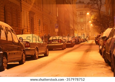 Winter city center street at night with parked cars covered by snow - stock photo