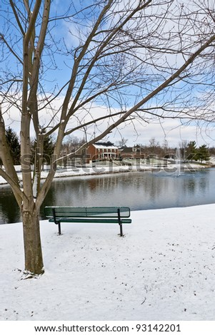 Winter city scene with a bench near pond  at neighborhood recreation area.