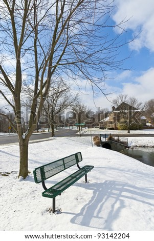 Winter city scene with a bench near pond  at neighborhood recreation area. - stock photo