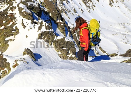 Winter climber on snowy mountain ridge in fine day