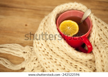 Winter cold sickness concept: A cup of hot tea and lemon wrapped with a woolen scarf - stock photo