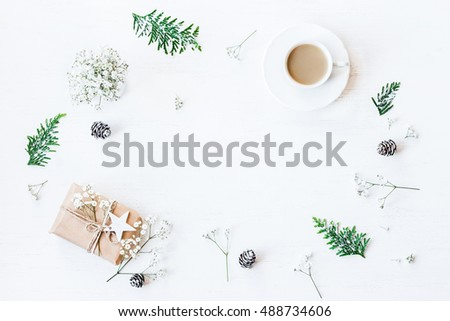 Winter composition. Cup of coffee, christmas gift, pine cones, thuja branches and gypsophila flowers. Top view, flat lay