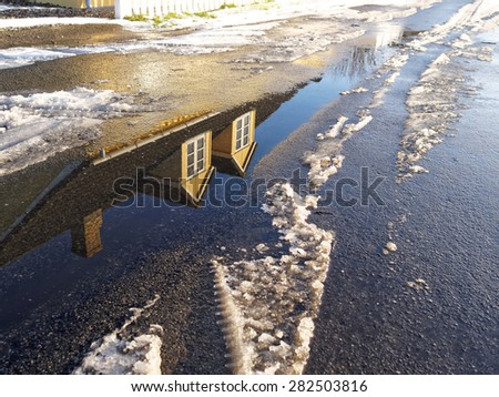 Winter concept background image house reflected in water pond and snow on the road   - stock photo