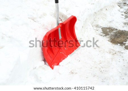 Winter concept. Red shovel for snow removal - stock photo