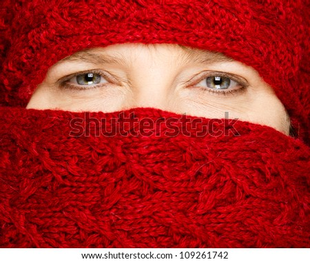 Winter concept with middle-aged woman wrapped up in red scarf - stock photo