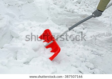 Winter concept. Woman hand removing snow with red shovel - stock photo