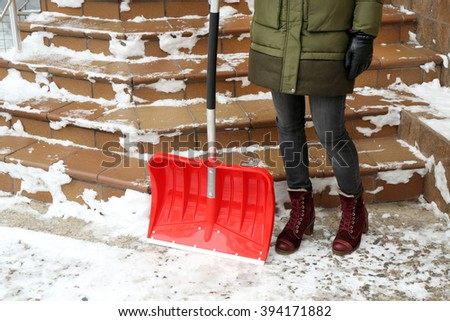 Winter concept. Woman removing snow with red shovel - stock photo