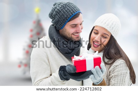 Winter couple holding gift against blurry christmas tree in room - stock photo