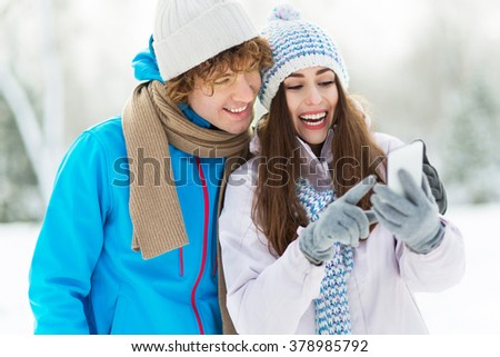 Winter couple with mobile phone