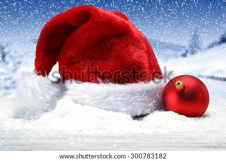 winter decoration of snow red ball and red hat on snow  - stock photo