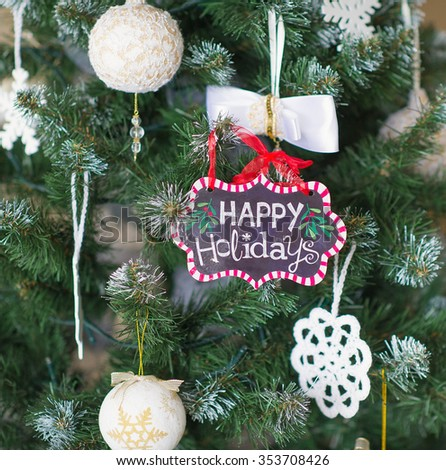 Winter decorations with Happy holidays sign hanging on branches of decorated Christmas tree - stock photo