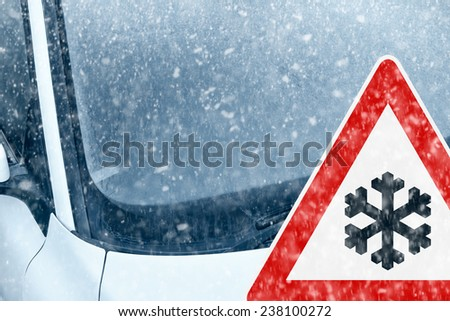 Winter Driving - Ice Covered Windshield with Warning Sign - Snow on an ice covered windshield with warning sign.  - stock photo