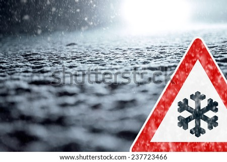 Winter Driving - Winter Road - Caution Snow - Abstract winter background with warning sign - Snow covered road at night. - stock photo