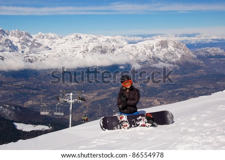 Winter entertainment/Smiling female snowboarder sitting on snow with mountains in the background - stock photo