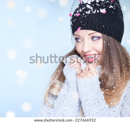 Winter face close up of young attractive woman wearing hat covered with snow flakes. Christmas concept. - stock photo