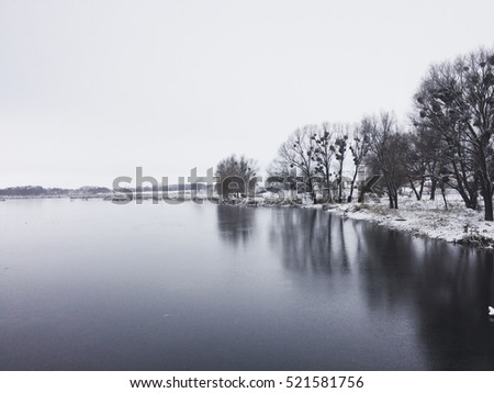 winter fairy tale, frozen river, a beautiful reflection of trees in water, bushes, reeds, iny