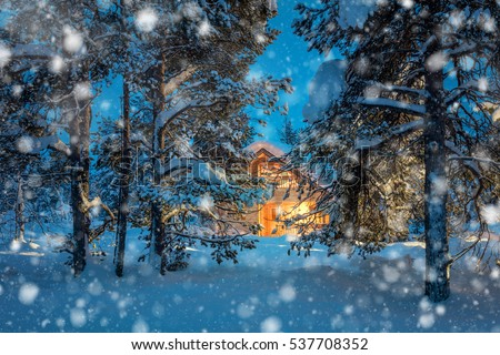 Winter fairytale night snowfall landscape - Wooden house with warm light in night snowy winter forest.
