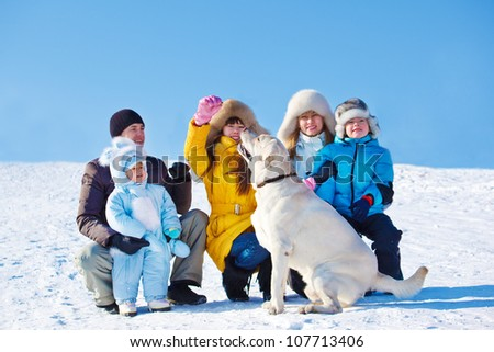 Winter family playing with Labrador Retriever