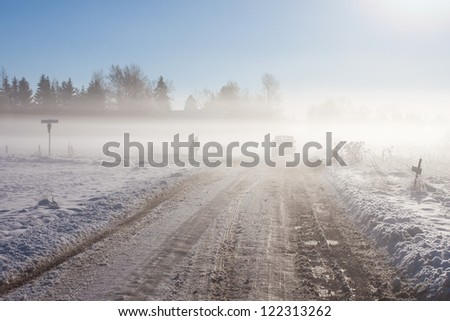 Winter farm road with off-road car and snow - stock photo