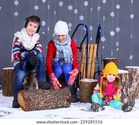 Winter Fashion. Adorable happy boy and girls in winter hat, gloves and sweater in studio. - stock photo