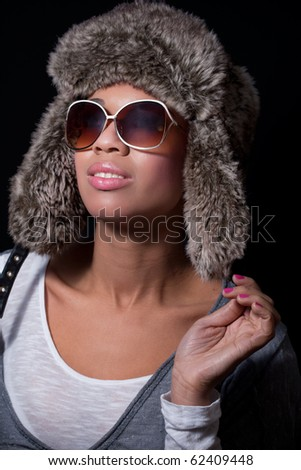 Winter fashion: beautiful happy woman wearing sunglasses and a fur hat, isolated on black