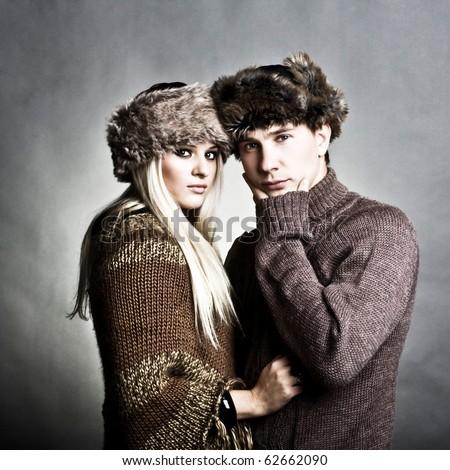 Winter fashion beautiful man and woman studio photo shooting - stock photo