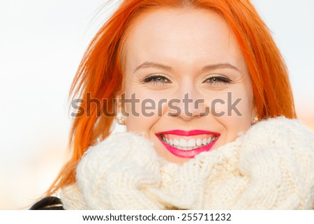 Winter fashion. Beauty face portrait red hair young woman in warm clothing outdoor enjoying sunlight on sunny day. - stock photo